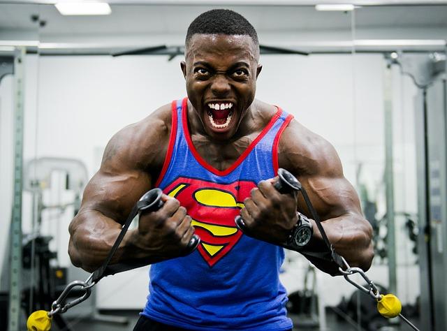Svalnatý muž, ktorý kričí, je v tričku so znakom supermana s posilňovni