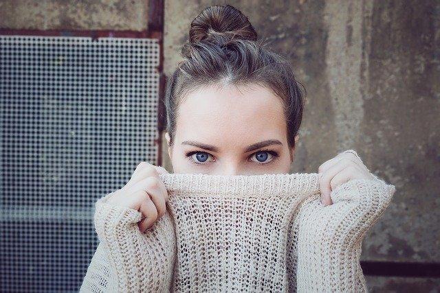 Žena s modrými očami si drží sveter pred tvárou.jpg