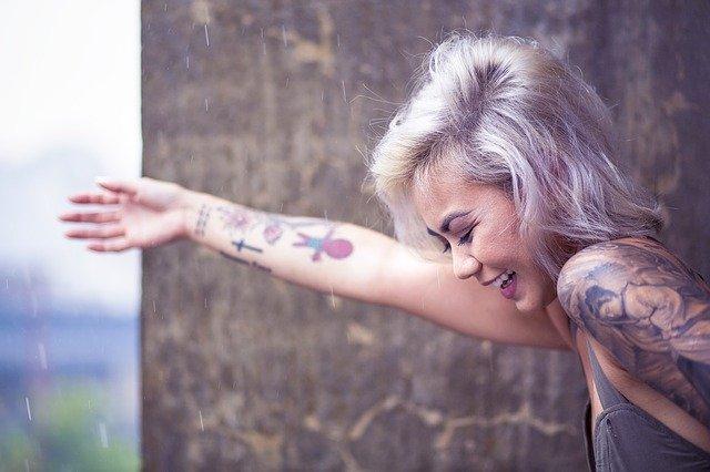 Žena s farebnými vlasmi a tetovaním sa smeje